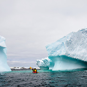 Kayakers in a tandem kayak glide past an iceberg that has been slowly tilting at Hydrurga Rocks at Two Hummock Island. The region is known as a favorite for leopard seals (Hydrurga leptonyx).