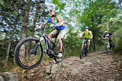 Three Mountainbikers stunt racing forest track