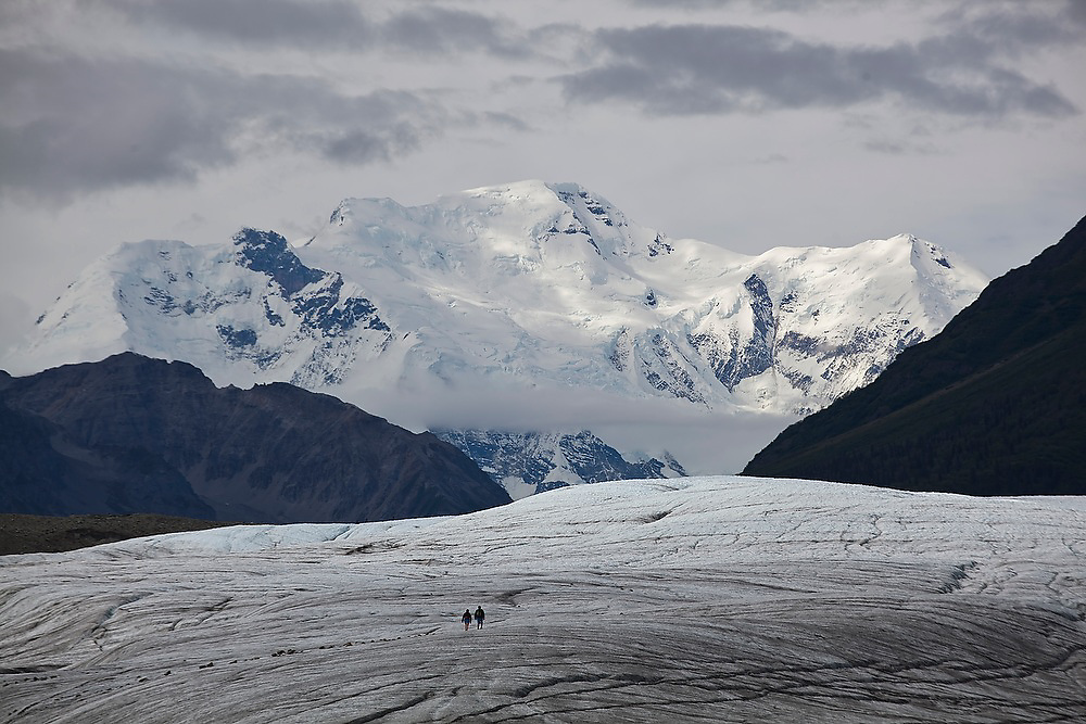 Two tourists are dwarfed by distant Mount Blackburn (4,996 m) as they walk across the surface of the Root Glacier in Wrangell-St. Elias National Park, Alaska.