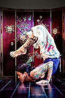 Dark haired woman doing scorpion pose in front of an asian panel.