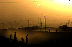 KANDAHAR,AFGHANISTAN - SEPT.6 :  Afghan children fly kites near a cemetery where Taliban are buried September 6, 2002 in Kandahar, Afghanistan. The city remains tense afterKandahar Governor Gul Agha Sherzai was shot during an apparent assassination attempt on President Hamid Karzai yesterday evening. .(Photo by Ami Vitale/Getty Images)