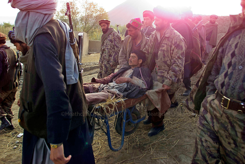 A wounded Northern Alliance soldier is carried by comrades on the outskirts of Taloquan .