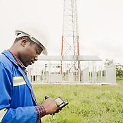 INDIVIDUAL(S) PHOTOGRAPHED: Chileshi Robertson. LOCATION: IHS Telecommunications Tower, Nkondora Village, Near Chongwe, Lusaka Province, Zambia. CAPTION: Standing in front of the tower, Chileshi checks key data on his smartphone.