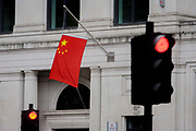 The Chinese national flag hangs from the Bank of China's offices in the City of London, England UK. Red traffic lights and the red of the flag a similar. At a time when economic and property investment agreements between Britain and China were confirmed, the Chinese communist state's presence in the UK capital is becoming more obvious.