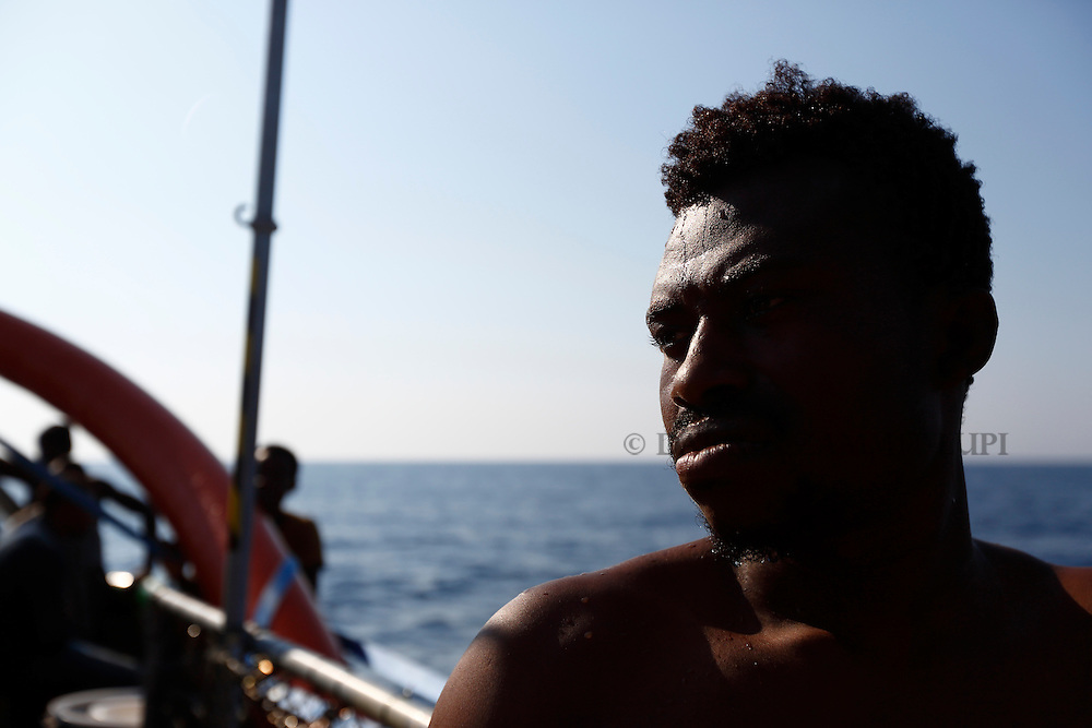 A migrant stands on the deck of the Medecins san Frontiere (MSF) rescue ship Bourbon Argos somewhere between Libya and Sicily August 8, 2015.  Some 241 mostly West African migrants on the ship are expected to arrive on the Italian island of Sicily on Sunday morning, according to MSF.<br /> REUTERS/Darrin Zammit Lupi <br /> MALTA OUT. NO COMMERCIAL OR EDITORIAL SALES IN MALTA