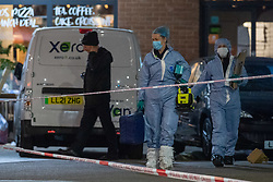 © Licensed to London News Pictures. 23/04/2021. London, UK. Forensic investigators inside a cordon on Barking Road in Canning Town following the fatal stabbing of a 14-year-old boy. Police were called at 15:56 BST on Friday, 23 April to reports of an assault in Barking Road, E16. Metropolitan Police officers attended with medics from the London Ambulance Service and the London Air Ambulance. They found a 14-year-old male who had been stabbed. He was pronounced dead shortly after 16:30 BST. Photo credit: Peter Manning/LNP