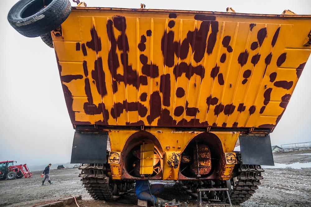 Rafal Flieger walks past as electrical engineer Jacek Renkas scrubs rust from the hull of a Soviet-era amphibious vehicle still in use at the Polish Polar Station in Hornsund, Svalbard.