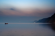Small red fishing boat inside the calm sea at twilight