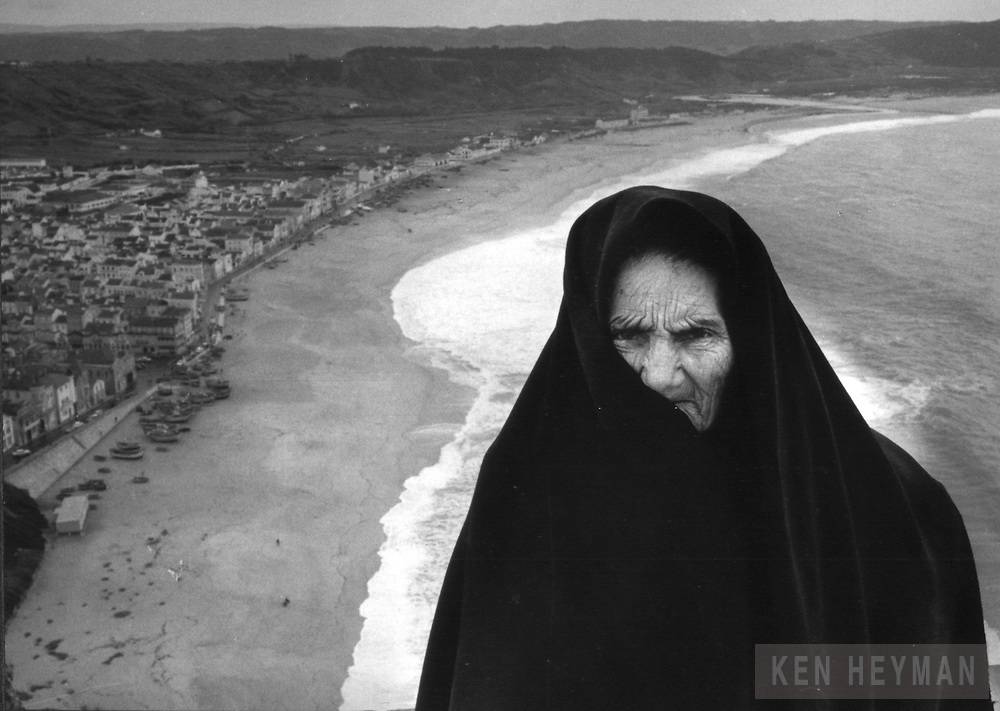 Nazare, Portugal, this woman is waiting to sell me crab legs.  I took a whole roll as the waves washed up behind her.