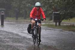 © Licensed to London News Pictures. 14/09/2021. London, UK. A woman cycles during heavy rain in Greenwich Park, South East London . A yellow weather warning for rain is in place in parts of England . Photo credit: George Cracknell Wright/LNP