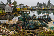 The lobster docks and pier piled high with traps on a foggy morning in the quaint fishing harbor of Port Clyde, Maine.