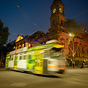 Melbourne Town Hall at night with city traffic