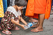 """22 JULY 2013 - PHRA PHUTTHABAT, THAILAND: A girl washes a monk's feet during the Tak Bat Dok Mai at Wat Phra Phutthabat in Saraburi province of Thailand, Monday, July 22. Wat Phra Phutthabat is famous for the way it marks the beginning of Vassa, the three-month annual retreat observed by Theravada monks and nuns. The temple is highly revered in Thailand because it houses a footstep of the Buddha. On the first day of Vassa (or Buddhist Lent) people come to the temple to """"make merit"""" and present the monks there with dancing lady ginger flowers, which only bloom in the weeks leading up Vassa. They also present monks with candles and wash their feet. During Vassa, monks and nuns remain inside monasteries and temple grounds, devoting their time to intensive meditation and study. Laypeople support the monastic sangha by bringing food, candles and other offerings to temples. Laypeople also often observe Vassa by giving up something, such as smoking or eating meat. For this reason, westerners sometimes call Vassa the """"Buddhist Lent.""""     PHOTO BY JACK KURTZ"""