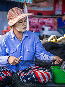 30 APRIL 2013 - MAHACHAI, SAMUT SAKHON, THAILAND:   A Burmese worker with thanaka powder on her face repairs a fishing net in the port of Mahachai, Samut Sakhon province, Thailand. The Thai fishing industry is heavily reliant on Burmese and Cambodian migrants. Burmese migrants crew many of the fishing boats that sail out of Samut Sakhon and staff many of the fish processing plants in Samut Sakhon, about 45 miles south of Bangkok. Migrants pay as much $700 (US) each to be smuggled from the Burmese border to Samut Sakhon for jobs that pay less than $5.00 (US) per day. There have also been reports that some Burmese workers are abused and held in slavery like conditions in the Thai fishing industry. Thanaka powder has been used by Burmese for over 2000 years for protection from the sun.         PHOTO BY JACK KURTZ