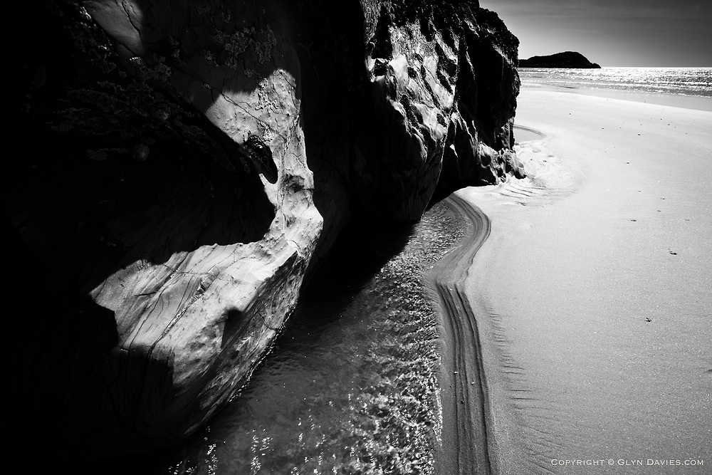 Black, shiny, eroded and smoothed pillow lavas surrounded by soft sand and sea water at a vast beach at Llanddwyn Island off Anglesey