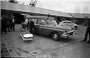 """25/06/1963<br /> 06/25/1963<br /> 25 June 1963<br /> Ford station wagon Ambulance being unloaded from the ship the """"City of Cork"""" at the North Wall, Dublin port. Image shows the ambulances stretcher being demonstrated. Note the Beatle needing a push start and a truck of """"Patz"""" lager."""