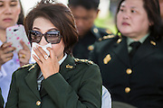 29 SEPTEMBER 2014 - NAKHON NAYOK, NAKHON NAYOK, THAILAND: A Thai army Lt. Colonel holds her nose as exhaust fumes from a Thai armored unit drifts over the crowd during the retirement ceremony for more than 200 Thai generals including Gen. Prayuth Chan-ocha, who led the 22 May coup against the civilian government earlier this year. Prayuth has been chief of the Thai army since 2010. After his retirement, Gen. Prayuth will retain his posts as head of the junta's National Council for Peace and Order (NCPO) and Prime Minister of Thailand. Under Thai law, military officers must retire at 60 years of age. The 200 generals who retired with Prayuth were also his classmates at the Chulalomklao Royal Military Academy in Nakhon Nayok.    PHOTO BY JACK KURTZ