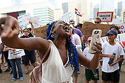 A demonstrator reads a poem for the people attending the Familes Belong Together rally at City Hall in downtown Dallas Tx. The rally was part of nationwide protest against the Trump administration policy of separating children from their parents when they cross the border into the US to request asylum.