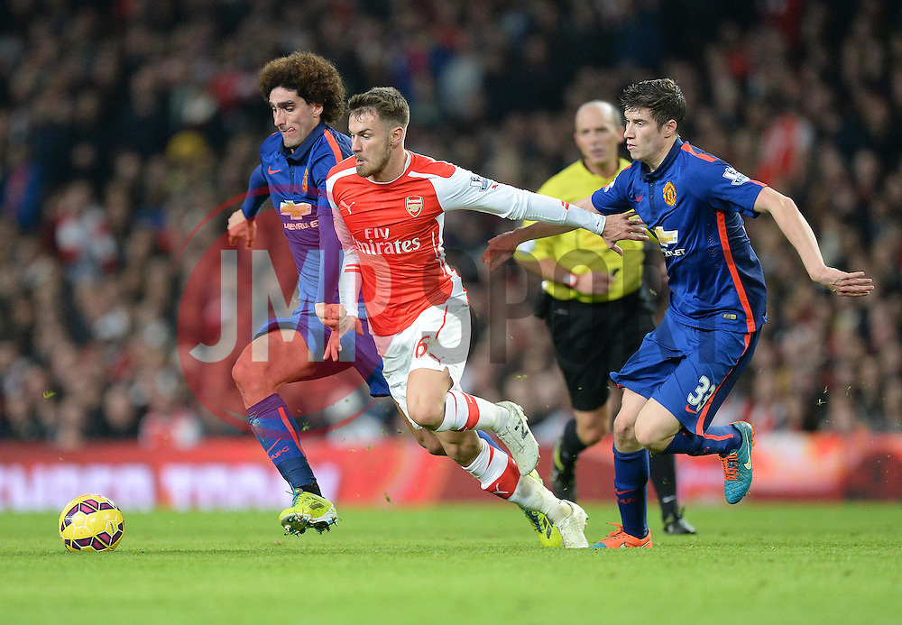 Arsenal's Aaron Ramsey battles for the ball with Manchester United's Marouane Fellaini - Photo mandatory by-line: Alex James/JMP - Mobile: 07966 386802 - 22/11/2014 - Sport - Football - London - Emirates Stadium - Arsenal v Manchester United - Barclays Premier League