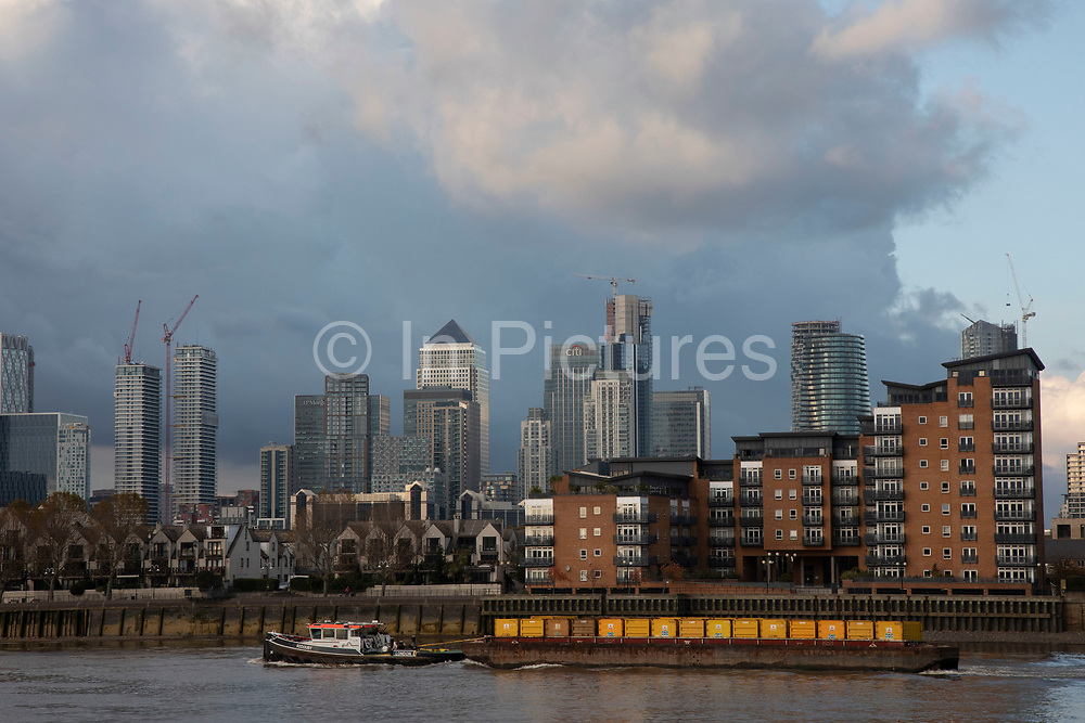 View looking across the River Thames towards Canary Wharf and the Docklands financial district as a waste barge is transported by small tug boat on 5th November 2019 in London, England, United Kingdom. Canary Wharf is the secondary central business district of London and is situated on the Isle of Dogs. It is one of the main financial centres in the world, containing many of the tallest buildings, including the second-tallest in the UK, One Canada Square.