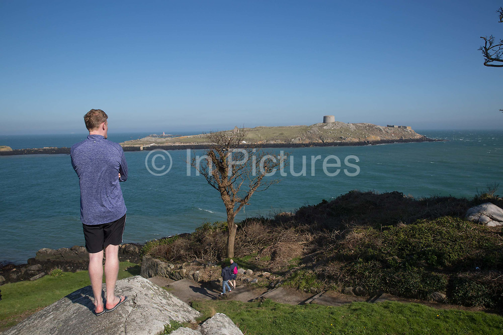 A man at Dillon's Park overlooks Dalkey Island on 08th April 2017 in County Dublin, Republic of Ireland. Dalkey is one of the most affluent suburbs of Dublin, and a seaside resort just south of Dublin. It was founded as a Viking settlement and became an active port during the Middle Ages.