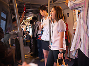 14 JULY 2011 - BANGKOK, THAILAND:   A woman yawns while riding the BTS Skytrain in Bangkok. The Bangkok Mass Transit System, commonly known as the BTS Skytrain, is an elevated rapid transit system in Bangkok, Thailand. It is operated by Bangkok Mass Transit System Public Company Limited (BTSC) under a concession granted by the Bangkok Metropolitan Administration (BMA). The system consists of twenty-three stations along two lines: the Sukhumvit line running northwards and eastwards, terminating at Mo Chit and On Nut respectively, and the Silom line which plies Silom and Sathon Roads, the Central Business District of Bangkok, terminating at the National Stadium and Wongwian Yai. The lines interchange at Siam Station and have a combined route distance of 55 km.    PHOTO BY JACK KURTZ