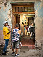 A local hub, with family and friends hanging out at a local barber shop in Havana.