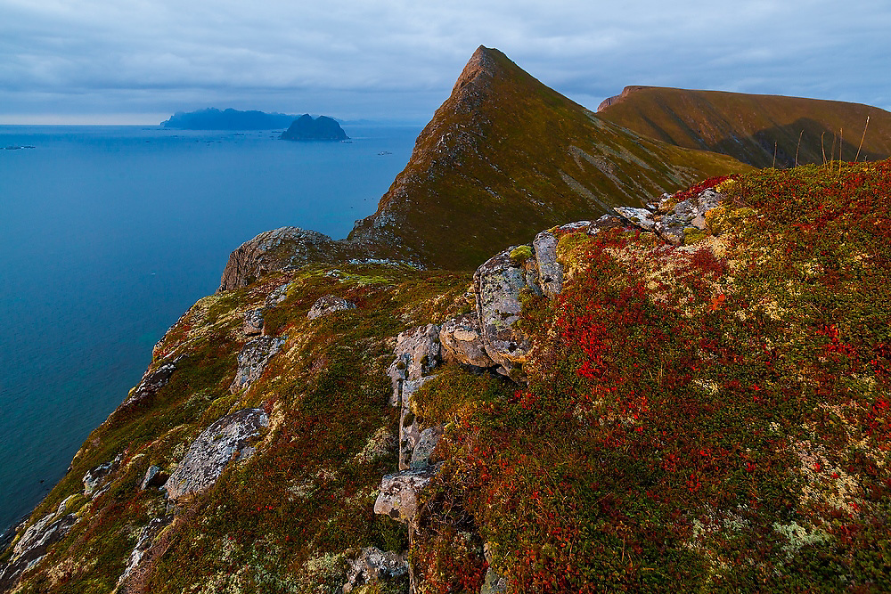 The crest of Vaeroy Island and the islands of Moskenesoya (left) and Mosken in the distance at sunset, Lofoten Islands, Norway.