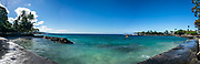 The seawall of Kailua-Kona city extends a protective arm around Niumalu (Kanuha) Beach  (next to Hulihee Palace hidden in palms on left) on Kailua Bay, Kona Coast, the Big Island, Hawaii, USA. This image was stitched from multiple overlapping images.
