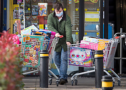 © Licensed to London News Pictures. 03/11/2020. Watford, UK. A man pushes two trolley loads of toys from a toy shop in Watford, as shoppers scramble to buy goods before  a second national lockdown comes in to place later this week. Strict measures are due to be re-introduced in an attempt to fight a second wave of the COVID-19 strain of Coronavirus. Photo credit: Ben Cawthra/LNP