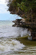 Water splashes against rocks on shore. Isle View Park, Northport, Door County, Wisconsin, USA.