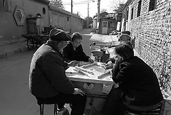 People playing Mahjong in a hutong in Beijing China