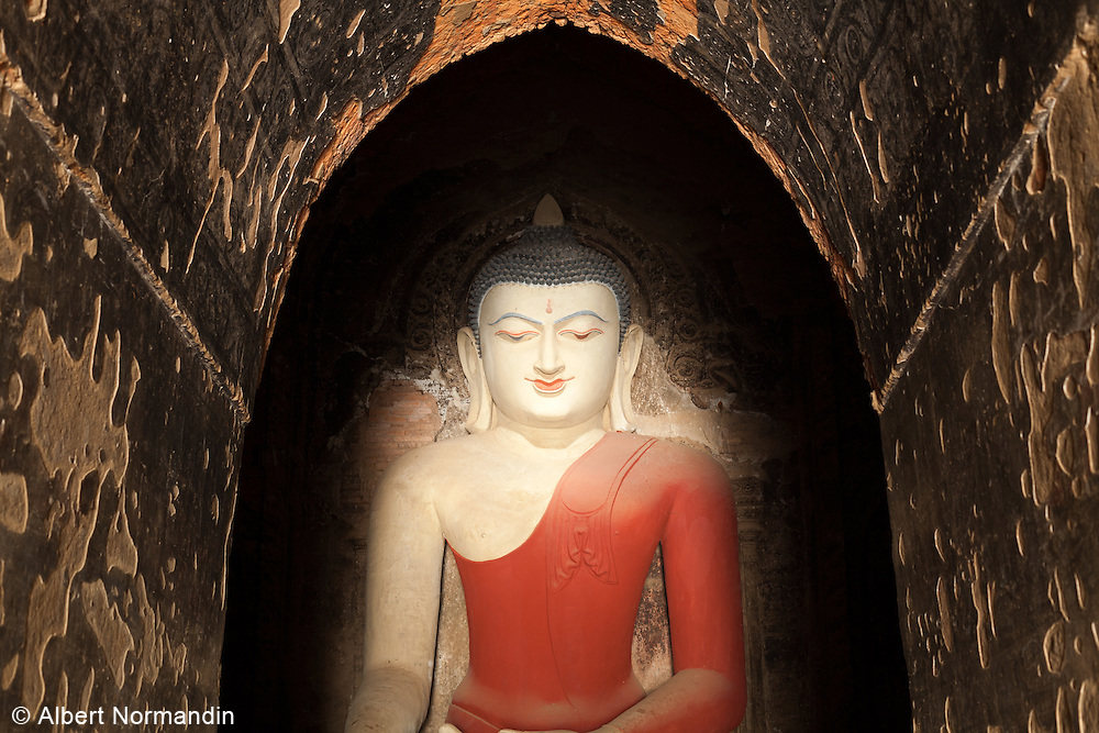 Buddha statue in archway of Pahto-thamya Pagoda, light coming from entrance way, Bagan