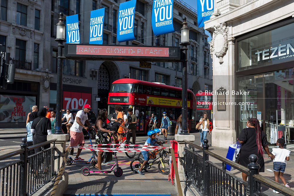 With a further 184 reported UK Covid deaths in the last 24 hrs, a total now of 43,414, a family ride their bikes and scooter through a busy Oxford Circus during the Covid pandemnic lockdown, now easing after three months of the Stay At Home policy but now being relaxed as the shops re-open, on 26th June 2020, in London, England. Government restrictions on the 2 metre rule is to be realxed on 4th July and replaced with 'one metre plus' in the hope it stimulates the struggling UK economy.
