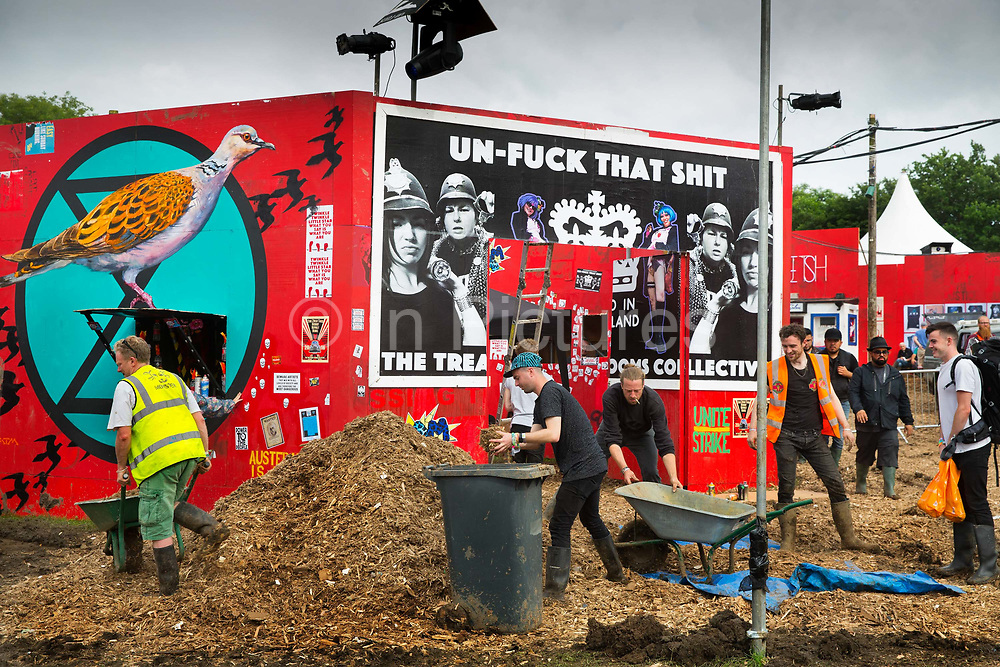 Workers making final preparations, putting woodchip onto the muddy floor, in the Shangri La field, Glastonbury Festival 2016. The Glastonbury Festival is the largest greenfield festival in the world, and is now attended by around 175,000 people. Its a five-day music festival that takes place near Pilton, Somerset, United Kingdom. In addition to contemporary music, the festival hosts dance, comedy, theatre, circus, cabaret, and other arts. Held at Worthy Farm in Pilton, leading pop and rock artists have headlined, alongside thousands of others appearing on smaller stages and performance areas.