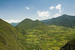 South America, Ecuador, Pululahua Crater and Geobotanical Reserve, view down into 34km crater of extinct volcano, with lush fields and small settlements.