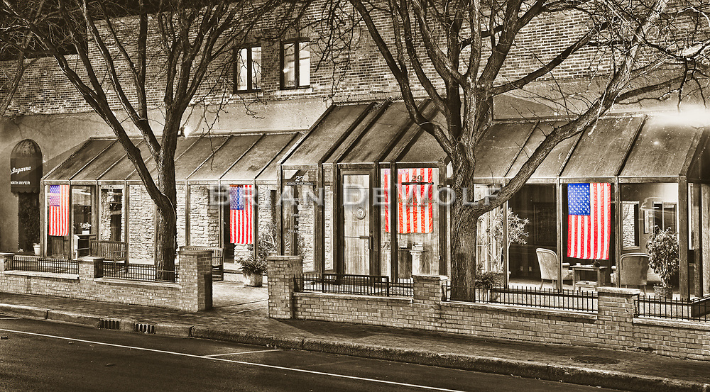 Backlit at night, American flags hang in the window of former 14 District Congressman Foster's Batavia, Illinois office.