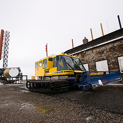 Bulldozer with communications satellite dishes in the background