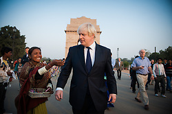 London Mayor Boris Johnson is chased by street vendors at India Gate in New Delhi, on the first of a six-day tour of India, where he will be trying to persuade Indian businesses to invest in London, Sunday November 25, 2012. Photo by Andrew Parsons / i-Images