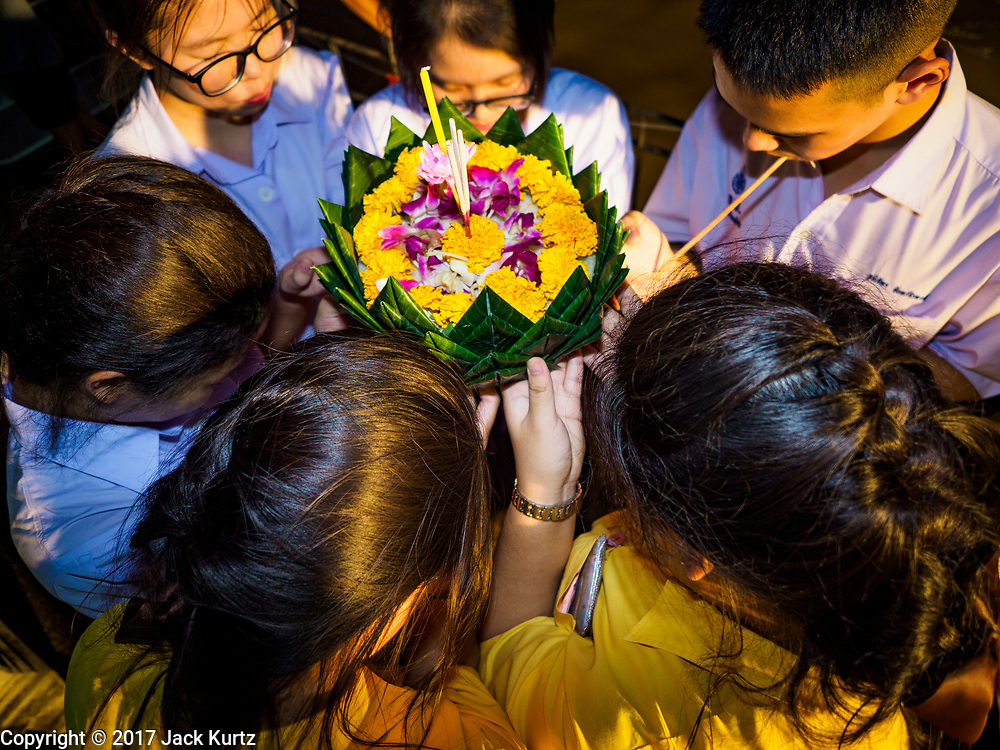 """03 NOVEMBER 2017 - BANGKOK, THAILAND: Girls pray before floating their krathong during Loi Krathong at Wat Prayurawongsawat on the Thonburi side of the Chao Phraya River. Loi Krathong is translated as """"to float (Loi) a basket (Krathong)"""", and comes from the tradition of making krathong or buoyant, decorated baskets, which are then floated on a river to make merit. On the night of the full moon of the 12th lunar month (usually November), Thais launch their krathong on a river, canal or a pond, making a wish as they do so. Loi Krathong is also celebrated in other Theravada Buddhist countries like Myanmar, where it is called the Tazaungdaing Festival, and Cambodia, where it is called Bon Om Tuk.     PHOTO BY JACK KURTZ"""