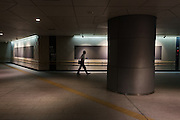 A salaryman or male office worker uses a smart phone as he walks through an underground passage near Yurakucho station, Tokyo, Japan. Friday July 22nd 2016