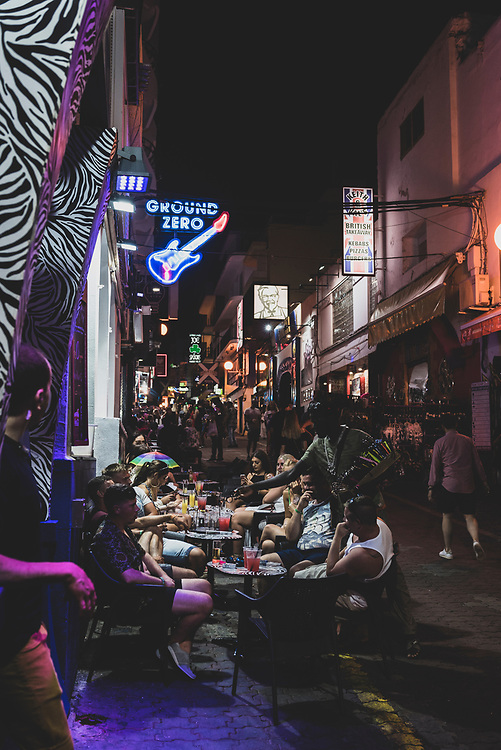 San Antonio, Ibiza, Spain - July 29, 2018: A group of young adults enjoy drinks on a street, Carrer de Santa Agnès, in San Antonio, Ibiza. The city of San Antonio, or Sant Antoni de Portmany, is especially popular with visitors from the United Kingdom.