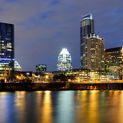 Panorama of Austin's city skyline at dusk, with the lights reflecting on the water and the Congress Street Bridge at right.