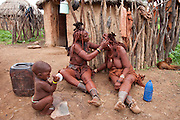 Viahondjera Musutua (left), a Himba tribeswoman, fixes her friend's hair while her child plays outside their house in the small village of Ondjete in northwestern Namibia. (Viahondjera Musutua is featured in the book What I Eat: Around the World in 80 Diets.) MODEL RELEASED.