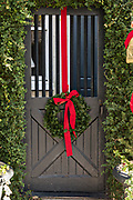 The wooden garden gate of a historic home decorated with a Christmas wreath on Meeting Street in Charleston, SC.
