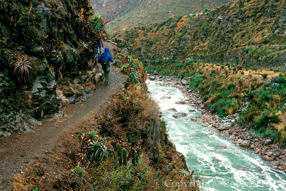 PERU, HIKING INCA TRAIL Hikers on the Inca Trail passing above the rapids of the Urubamba River near Chilca on the way to Machu Picchu