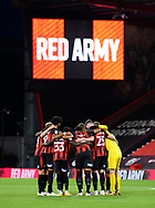 The Bournemouth players huddle before kick off with the big screen showing Red Army during the EFL Cup match between Bournemouth and Crystal Palace at the Vitality Stadium, Bournemouth, England on 15 September 2020.