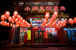 "Many neon signs and red lanterns at night outside restaurants on ""Ghost Street"" in Beijing 2009"