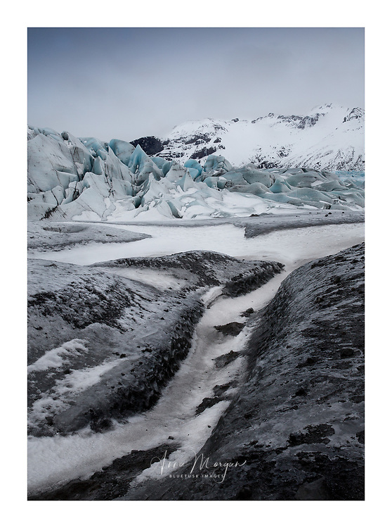 Glacial sediments deposited by meltwater at a glacial terminus in coastal Iceland with a layer of snow creating meandering patterns