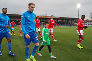 AFC Wimbledon midfielder Mitchell (Mitch) Pinnock (11) and Mascotduring the EFL Sky Bet League 1 match between AFC Wimbledon and Barnsley at the Cherry Red Records Stadium, Kingston, England on 19 January 2019.